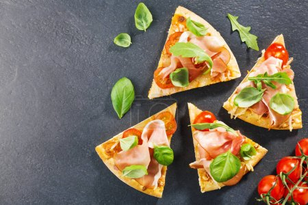 Photo for Top view of sliced delicious italian pizza with ham on black stone slate - Royalty Free Image