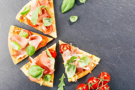 top view of sliced delicious italian pizza with ham on black stone slate