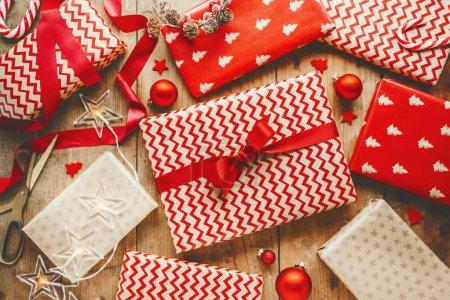 Photo pour Pose plate de cadeaux de Noël enveloppés dans du papier artisanal rouge sur une table en bois - image libre de droit
