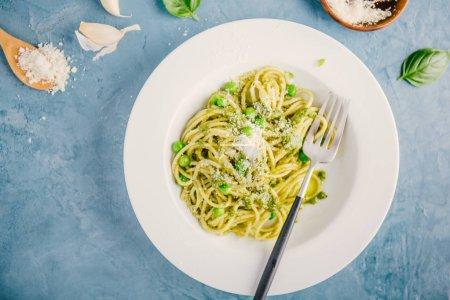 Photo pour Vue de dessus de spaghettis de savoureuses pâtes appétissantes avec pesto sauce douce, pois verts et fromage servi sur plaque sur table bleue - image libre de droit