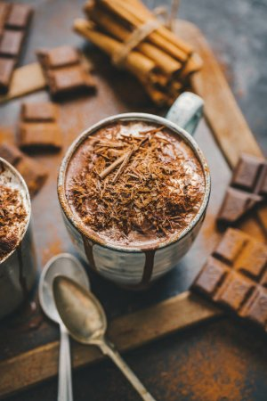 Photo for Close-up shot of hot chocolate with chocolate chunks in small cups served on dark table - Royalty Free Image