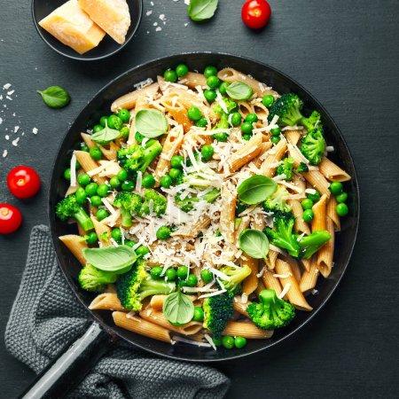 Photo pour Gros plan de grains entiers de délicieuses pâtes italiennes sain avec brocoli, pois verts, basilic et parmesan sur pan. Horizontal. - image libre de droit