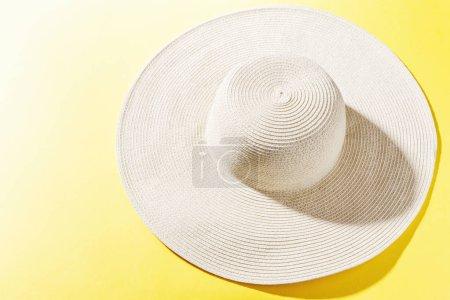 Photo pour Summer concept flat lay. Straw hat on bright yellow background. Horizontal. Closeup. - image libre de droit