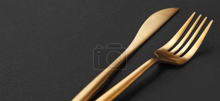 Photo pour Beaux couverts en or - fourchette et couteau sur plaque noire sur fond noir. Gros plan. Horizontal . - image libre de droit