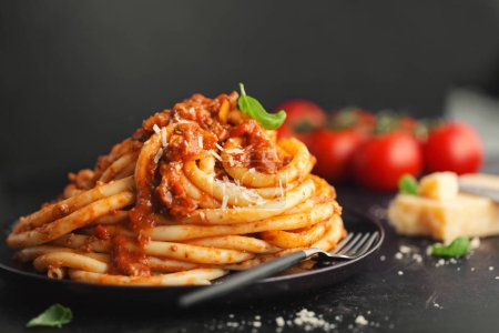 Photo pour Closeup of tasty appetizing pasta bolognese with cheese on dark background. - image libre de droit