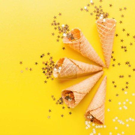 Foto de Ice cream cones with golden shining stars on yellow background. Party Happy Birthday Anniversary Background. Square. - Imagen libre de derechos