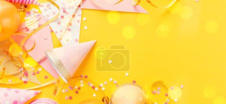 Photo for Colorful happy birthday or party background Flat Lay wtih birthday hats, confetti and ribbons on yellow background. Horizontal. - Royalty Free Image