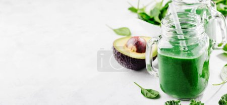 Photo for Fresh made healthy green smoothie served in jars on bright table. Fruits and vegetables ingredients around. Closeup with Copy space. Horizontal. - Royalty Free Image