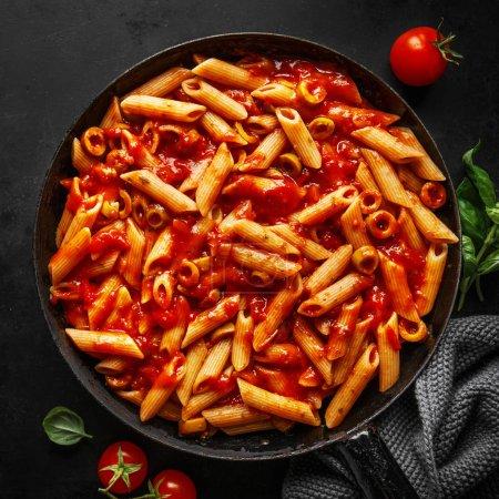 Photo pour Penne de savoureuses pâtes appétissantes avec sauce tomate et olives servis sur pan. Fond sombre. Place. - image libre de droit