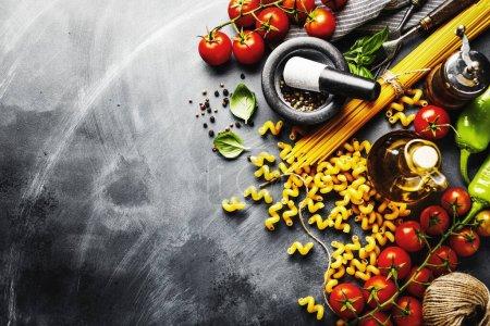 Photo pour Fond alimentaire italien avec des ingrédients pour cuisiner sur fond sombre. Vue d'en haut. Concept de cuisson . - image libre de droit