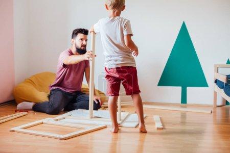 Photo pour Père et fils travaillent sur menuiserie à domicile dans la chambre de l'enfant - image libre de droit