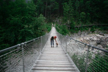 Photo for Young adventurous woman traveller in hipster millennial outfit, denim jeans and red beanie stands in middle of hanging bridge at exotic travel location, camping nomad lifestyle with dog - Royalty Free Image