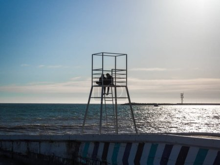Photo for Silhouette of a loving couple on a lifeguard tower on the beach - Royalty Free Image
