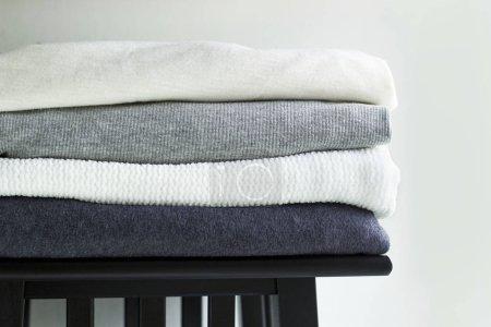 Szczelnie-do góry stos złożonych ubrań monochromatyczne na białym tle ściany. Czarny, szary i biały tkaniny Odzież na drewnianej półce.