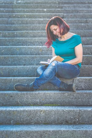 Photo pour Woman in casual outfit sitting on stairs reading book outdoor - image libre de droit