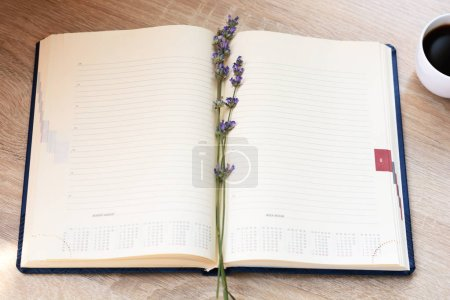 Open notebook, fountain pen and flowers (lavender) on the desktop.