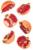 creative fruit concept. pomegranates halves flying in the air isolated on white with clipping path. levity concept fruit