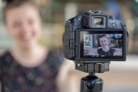 Photo pour Une jeune fille caucasienne faisant un blog vidéo (vlog) derrière la caméra - image libre de droit