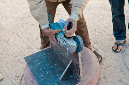 Cropped view of labor cutting tile outdoor using electric tool