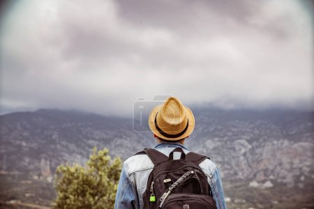 Photo for Young traveller enjoying a looking at sunset on Panoramic mountains view. Traveling, active lifestyle concept - Royalty Free Image