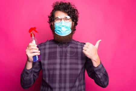 Photo of man wearing medicinal mask and holding ha...