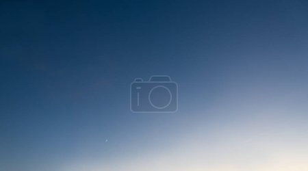 Photo for Crescent moon in a graduated blue sky. - Royalty Free Image
