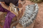Woman in Laos making cutlery and jewellery using scrap aluminium salvaged from unexploded ordnance dropped during U.S. secret war.