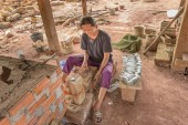 PHONSOVAN, LAOS - JANUARY 29, 2019: woman making war spoons using scrap aluminium salvaged from unexploded ordnance dropped during the U.S. secret war.