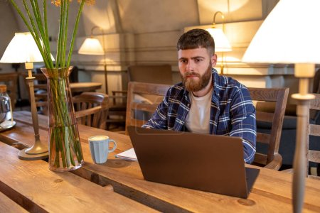 Photo for Young professional surfing the Internet on his laptop with cup of coffee on table at coffee shop or home office, working from cafe concept - Royalty Free Image