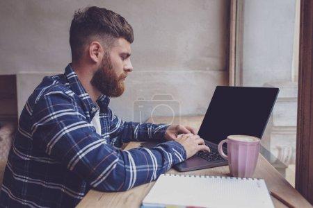 Photo pour Jeune homme bavarder via net-book pendant la pause de travail dans le café, mâle assis devant ordinateur portable ouvert avec écran d'espace de copie vierge pour votre message texte ou contenu publicitaire - image libre de droit