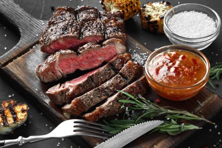Photo for Sliced grilled medium rare beef steak served on wooden board Barbecue, bbq meat beef tenderloin. Top view, slate background. - Royalty Free Image