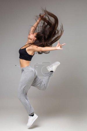 Photo pour Danseuse de style moderne posant sur fond de studio. La danse. Hobby. Hip hop, jazz funk, dancehall - image libre de droit
