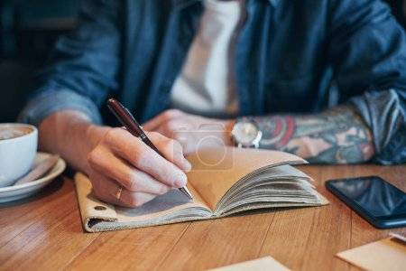 Man hand with pen writing on notebook on a wooden table. Close-up