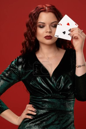 Photo for Young sexy woman with a red curly hair, have brought a playing cards to her face, on a red background. Poker - Royalty Free Image