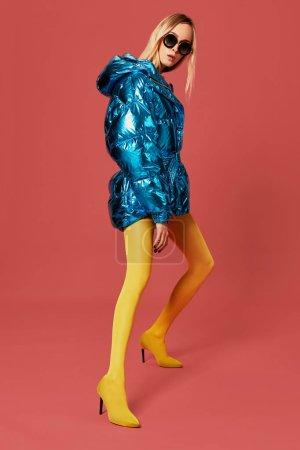 Photo pour Photo de mode de fille blonde émotionnelle posant sur la caméra en veste chaude bleu vif, lunettes de soleil et bas jaunes. Style surdimensionné - image libre de droit