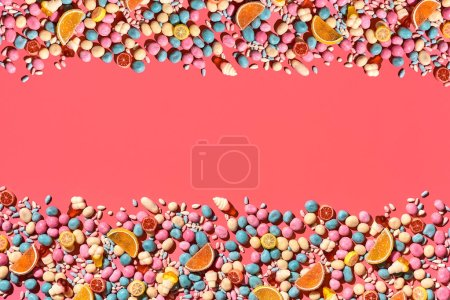 Various sweets, sweets are palced on the photo on the coral background