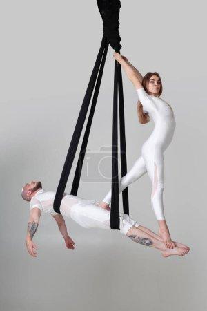 Photo pour Gymnases performance accroché sur une toile noire. Jolie fille et beau mec en costume de sport léger font des éléments acrobatiques dans un studio isolé sur fond blanc. Danse dans l'air avec - image libre de droit