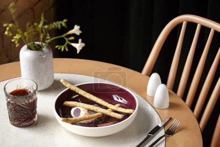 Photo pour Tourné d'un dessert gourmet sucré servi avec un verre sur une table chic avec des fleurs délicates sur elle. Menu délicieux. Vue panoramique, concept de cuisine de restaurant. - image libre de droit