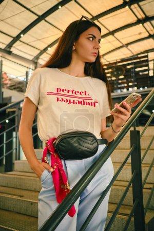 Photo pour Portrait en gros plan d'une jolie jeune brune se posant sur les marches d'un centre commercial, tenant son smartphone et regardant loin. Elle portait un t-shirt blanc portant l'inscription, un pantalon bleu, un sac noir à la taille. Nouvelle collection, mode - image libre de droit