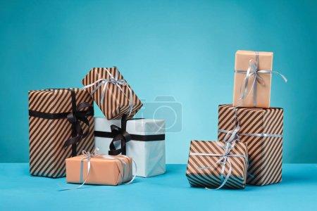 Photo pour Boîtes-cadeaux de différentes tailles, rayées et lisses, brunes, roses et blanches, attachées avec des arcs et des rubans noirs et argentés, sur une surface et un fond bleus. Concept de fêtes, fêtes, fêtes, félicitations, cadeaux, décorations, salutations - image libre de droit