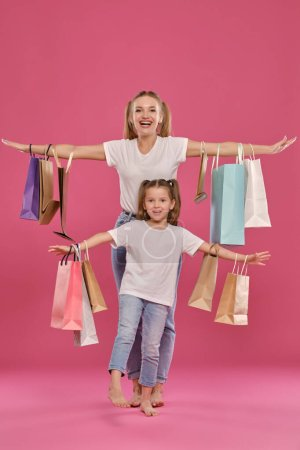 Photo pour Attractive blonde salope maiden and little girl with a funny ponytails are looking at the camera, spread their arms and smiling while posing against a pink studio background with many different sized colorful packages in their hands. Mère et fille dressées - image libre de droit