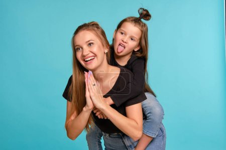 Photo pour Stylish blonde salope female and cute kid with a funny hairstyles, dressed in black shirts and blue denim jeans are posing against a blue studio background. Daughter is sitting on her mom back and showing her tongue, they are looking away and smiling. Fermé - image libre de droit