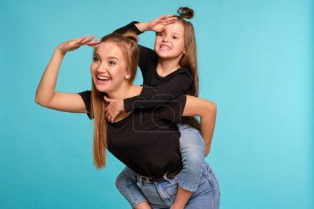Photo pour Stylish blonde salope woman and cute little girl with a funny hairstyles, dressed in black shirts and blue denim jeans are posing against a blue studio background. Daughter is sitting on her mom back, they are looking away and smiling. Gros plan. Sincère - image libre de droit