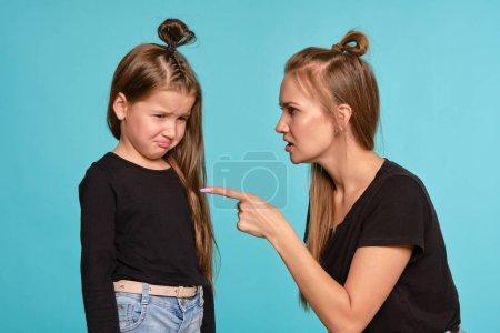 Photo pour Adorable blonde blonde jeune fille et petite fille avec une coiffure drôle, vêtue de chemises noires et jeans en denim se posent sur un fond de studio bleu. Maman réprimande sa fille. Gros plan. Concept des émotions sincères. - image libre de droit