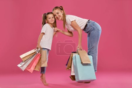 Photo pour Gorgeous blonde salope maiden and little girl with a funny ponytails are looking at the camera, smiling and holding each other hands while posing against a pink studio background with many different sized colorful packages in their hands. Maman et fille d - image libre de droit