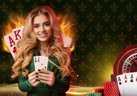 Photo pour Fille blonde souriante en robe élégante verte et bijoux. Elle montre deux cartes à jouer, posant sur fond coloré avec as, feu, roulette et piles de jetons. Poker, casino. Gros plan - image libre de droit