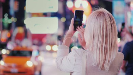 Photo for Tourist takes pictures with a smartphone on the famous Times Square in New York, rear view - Royalty Free Image