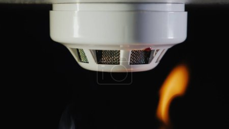 Photo for The smoke detector is triggered by a fire. Smoke and flames are visible. - Royalty Free Image