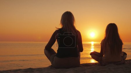 Photo for A woman with her daughter sitting side by side on the sand in a lotus pose, looking at the sunset over the sea. Health and happy time together. - Royalty Free Image