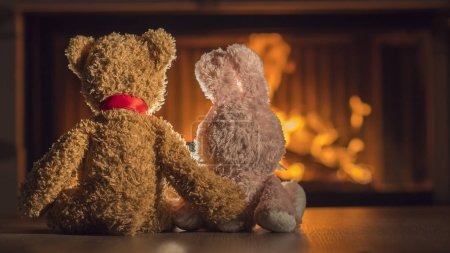Photo for Toy bear hugging a hare look at the burning fireplace. - Royalty Free Image